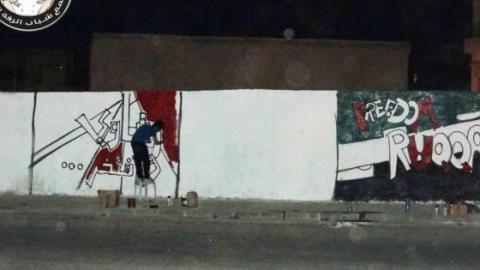 صورة رسام غرافيتي اثناء قيامه برسم جدارية في مدينة الرقة .... المصدر صفحة شباب الرقع الحرَ على الفيس بوك