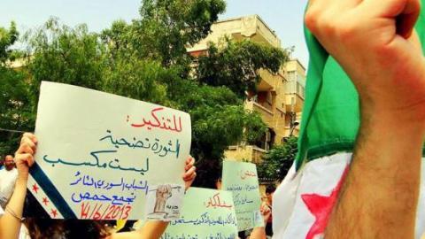 لافتة مرفوعة في أحد تظاهرات التجمع في مدينة حمص. المصدر: الصفحة الرسمية للتجمع