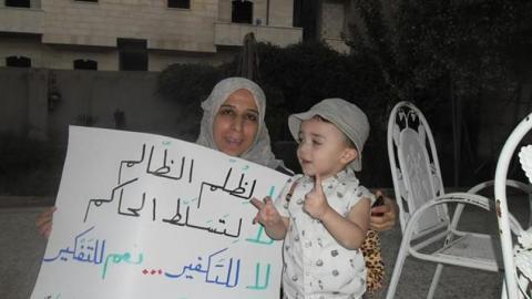 سعاد نوفل وهي ترفع لافتة برفقة أحد الأطفال. المصدر: الصفحة الرسمية لسعاد نوفل على الفيسبوك