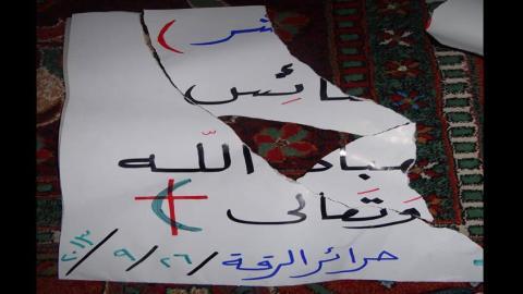 اللافتة التي مزقها عناصر داعش، وهي لافتة كتبتها سعاد تضامنا مع المسيحيين بعد إنزال داعش للصليب عن الكنيسة. المصدر: الصفحة الرسمية لسعاد على الفيسبوك