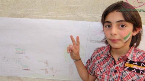 أحد الأطفال المشاركين في دورة التفريغ النفسي في المليحة وعلى وجهه علم الاستقلال(الثورة). المصدر: المنظمة السورية للمرأة والطفل
