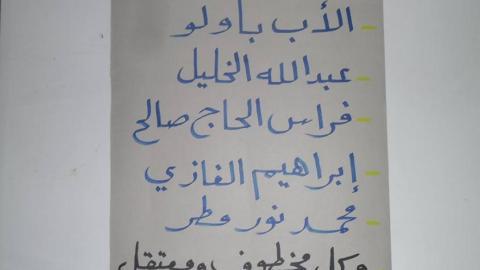 لافتة  عليها أسماء المعتقلين لدى داعش رفعتها الناشطة سعاد نوفل أمام مقرهم في الرقة، مطالبة بالإفراج عنهم تطالب فيها بالإفراج عنهم. المصدر: صفحة الناشطة سعاد نوفل على الفيسبوك