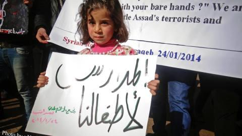 صورة لطفلة نازحة تحمل لافتة تطالب بفتح المدارس، المصدر الموقع الرسمي للحملة عالفيسبوك.