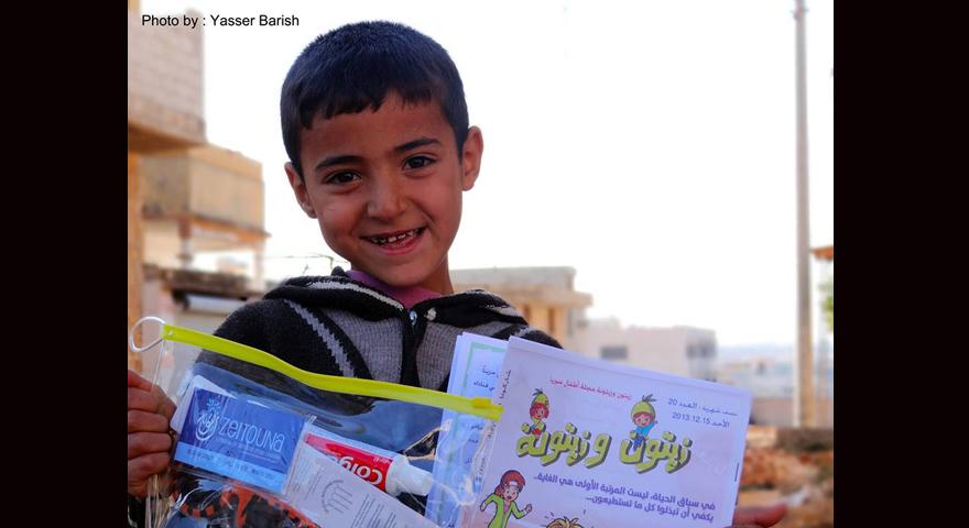 صورة طفل مع مجلة زيتون و زيتونة ضمن فعاليات الكرفان السحري....المصدر: الصفحة الرسمية للكرفان السحري على الفيسبوك