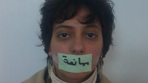 رزان غزاوي وهي تضع على فمها شريط لاصق مكتوب عليه ممانعة كدلالة على أن النظام الذي يقدم نفسه يقيد الحريات. المصدر: الصفحة الشخصية لرزان غزاوي على الفيسبوك