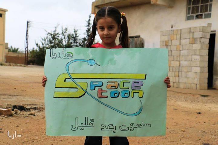 طفلة من داريا ترفع لافتة تخاطب من خلالها أطفال العالم. المصدر: مركز داريا الإعلامي