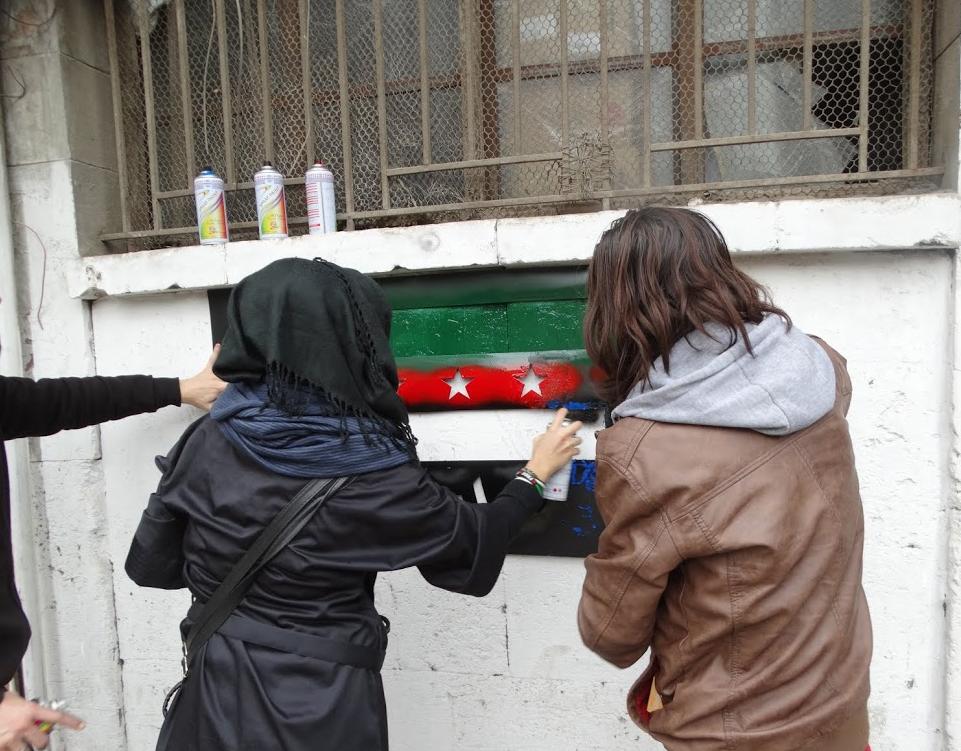 ناشطتان تقومان ببخ العلم على أحد جدران مدينة حلب. المصدر: مؤسسة اليوم التالي