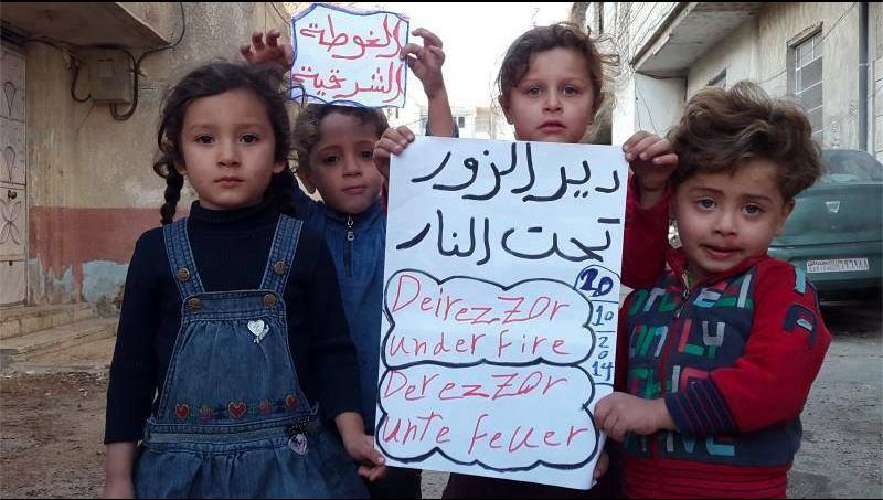 أطفال في أحد مخيمات اللجوء السورية يرفعون لافتة تضامنا مع دير الزور. المصدر: الصفحة الرسمية للحملة على الفيسبوك