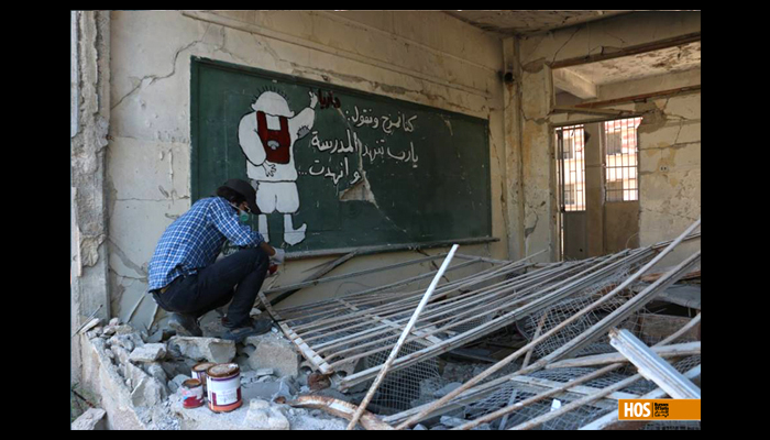 Abu Malik with one of his graffiti. Source: Humans of Syria.