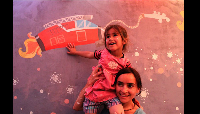 Diala Brisly with a child at Wazeh Camp in the Bekaa Valley, Lebanon