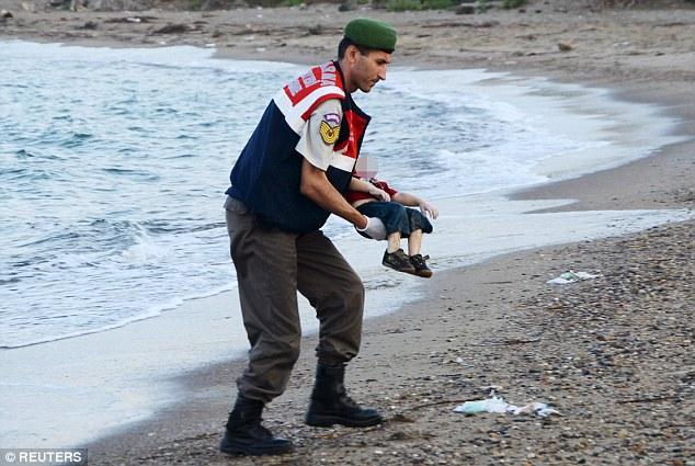 الشرطي التركي وهو يحمل جثة آلان