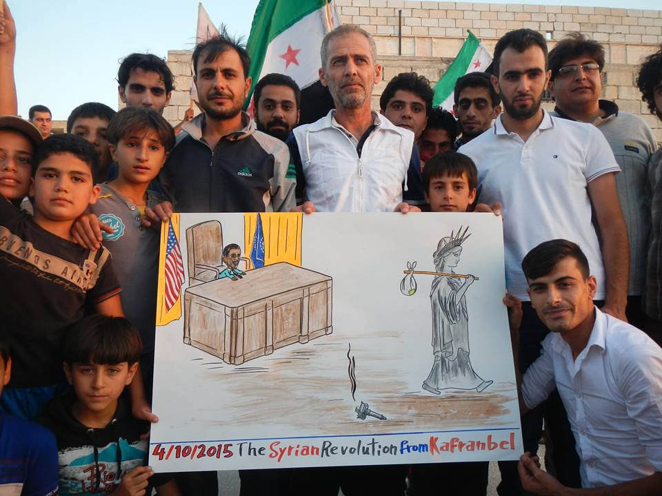 Protesters in Kafranbel holding up a poster satirizing the position of the U.S. in Syria following Russian intervention/Activist Raed Fares's Facebook page