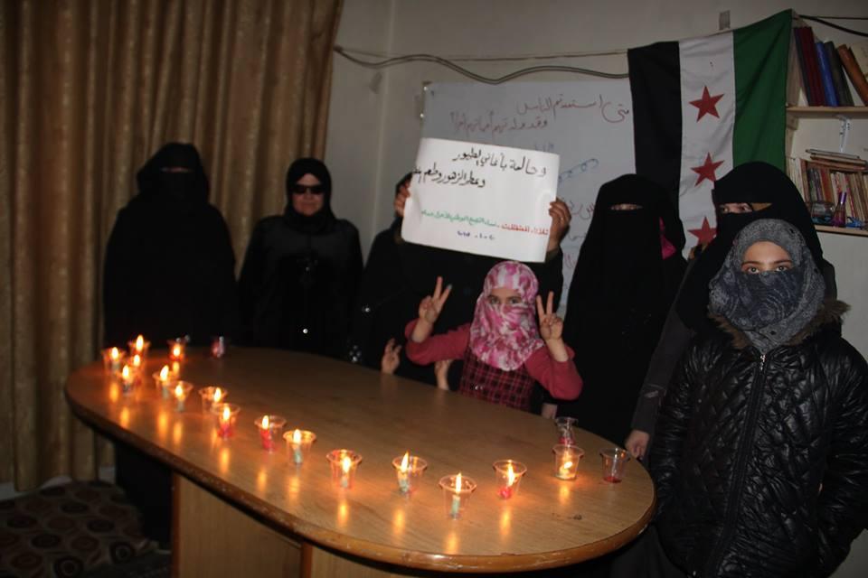 نساء التجمع يرفعن لافتة ويشعلن الشموع.المصدر: الصفحة الرسمية للتجمع على الفيسبوك