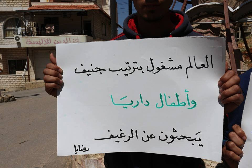 "[""As the world is busy planning the Geneva talks, children are looking for a loaf of bread,"" reads a sign held by a Madaya resident in solidarity with Darayya./Source: The Local Council of Darayya, Facebook - Madaya - 19-4-2016]."