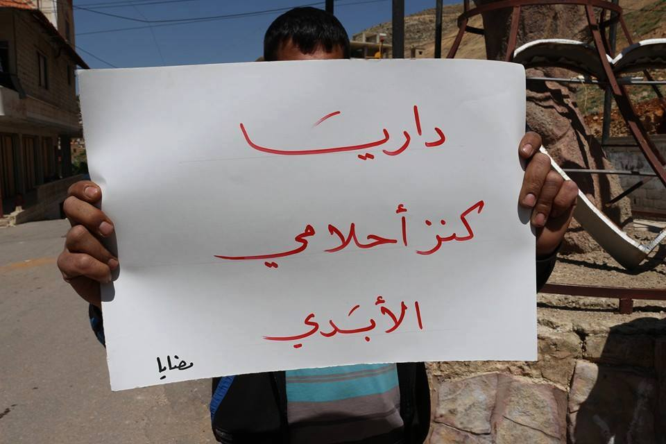 "[""Darayya: A treasure of my eternal dreams,"" reads a sign held by a resident of Madaya in solidarity with Darayya./Source: The Local Council of Darayya, Facebook - Madaya - 19-4-2016]."