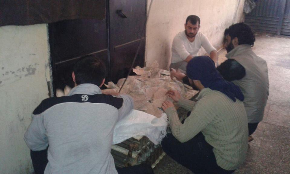 """المعتقلون يعالجون الخبز اليابس بعد قطع المواد الغذائية عنهم، المصدر: صفحة """"معتقلو سجن حماه المركزي""""، فيسبوك."""