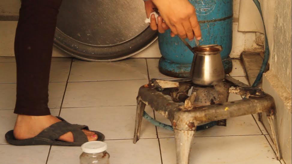 هدى التي فقدت رجلها تغلي القهوة في منزلها. المصدر: حكاية ما انحكت