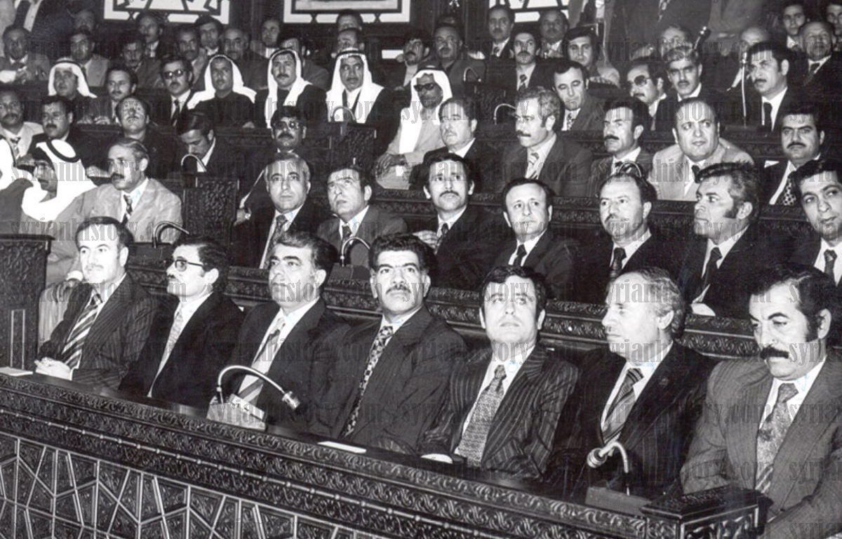 [Photo: Hafez al-Asad's first inauguration as President in the People's Council, March 1971. L–R: Asad, Abdullah al-Ahmar, Prime Minister Abdul Rahman Khleifawi, Assistant Regional Secretary Mohamad Jaber Bajbouj, Foreign Minister Abdul Halim Khaddam and People's Council Speaker Fihmi al-Yusufi. In the third civilian row are Defense Minister Mustafa Tlass (MP in the 1971 Parliament) and Air Force Commander Naji Jamil. Behind Tlass is Rifaat al-Assad, Assad's younger brother. On the far right in the fourth row is future vice president Zuhair Masharqa, and behind Abdullah al-Ahmar is Deputy Prime Minister Mohammad Haidar - Damascus (Syrian History Archive/Public Domain via Wikimedia Creative Commons)].
