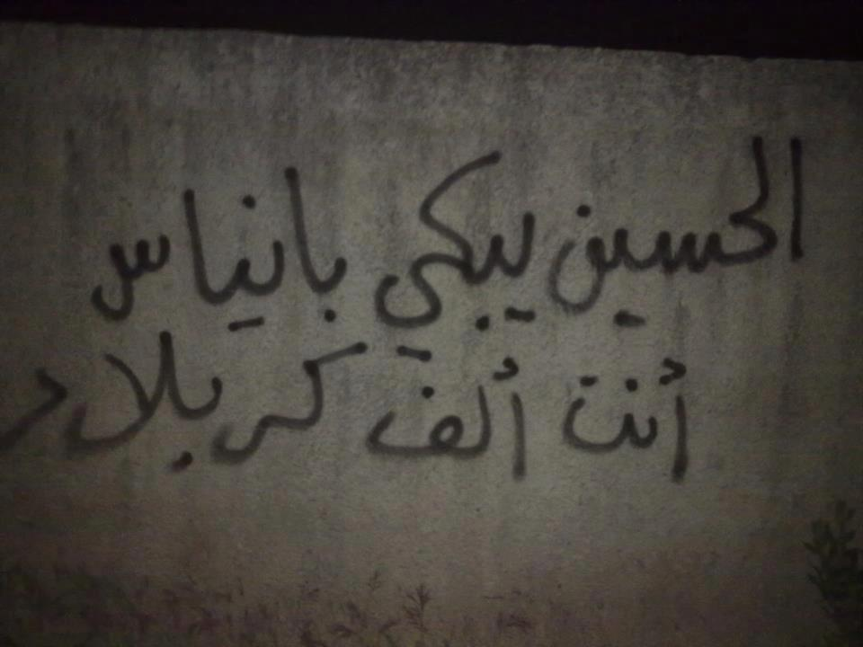"[Photo: A slogan written by Ayman in rural Jablah. It reads ""Husayn weeps Banyas, you are a thousand Karbala'"" (SyriaUntold)]."