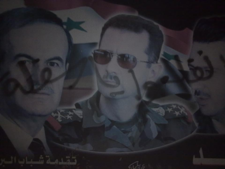 "[Photo: One of Ayman's graffiti on a poster that depicts the Asad family in rural Jablah. It reads ""Get Out You Varmints"" (SyriaUntold)]."