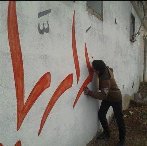 مواطن من مدينة داريا يقبل اسم مدينته المكتوب على الجدار قبل رحيله عنها. المصدر: المجلس المحلي لمدينة داريا)