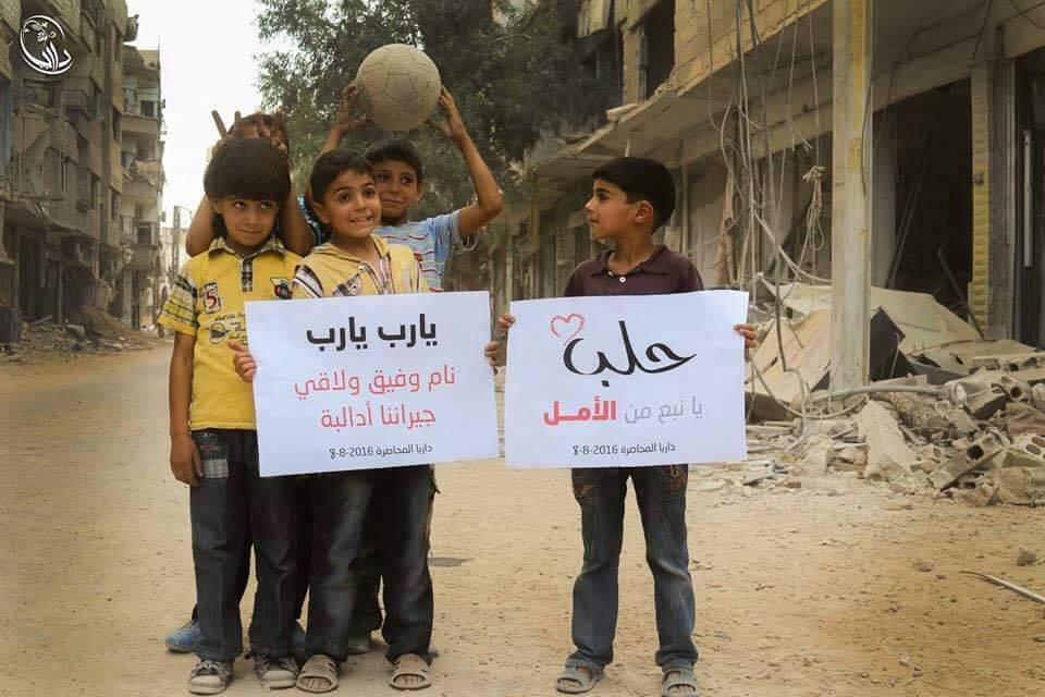 [Photo: Children in besieged Daraya (Rif Dimashq governorate) holding banners that celebrate the partial lifting of the siege of Aleppo - 8-8-2016 ( Local Council of Daraya Facebook page)].