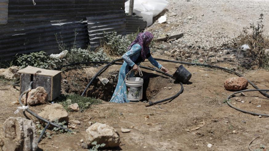 روعة، 21 عاما، أم لثلاثة أطفال من حلب، تسحب ماء من بئر في مخيم عشوائي للاجئين السوريين بوادي البقاع. البئر هو مصدر الماء الوحيد في المخيم وهو غير صالح للشرب. أخبر بعض السكان مجلس اللاجئين النرويجي أن من يشرب من البئر بشكل دائم يعاني من أمراض جلدية وآفات اخرى – لبنان – 24/7/2014 (سام تارلينغ/ مجلس اللاجئين النرويجي عبر CC BY-ND 2.0 )].