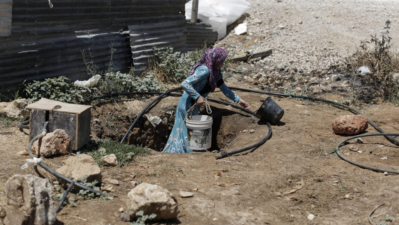 [Photo: Rawaa, 21, a mother of three from Aleppo, draws water from a well at an informal tented settlement for Syrian refugees in the Bekaa Valley. The well is the camp's only water source and is not clean enough to drink. Some residents told NRC (Norwegian Refugee Council) that those who drank from the well regularly suffered skin diseases and other complaints - Lebanon - 24-7-2014 (Sam Tarling/NRC via CC BY-ND 2.0)].