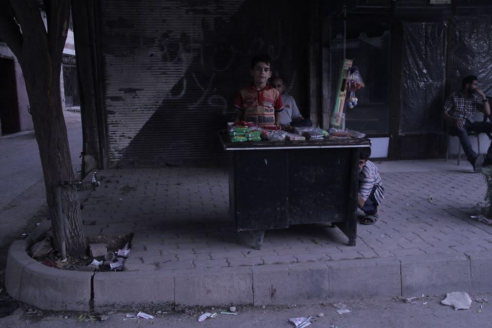 [Photo: A child-merchant in al-Qabun - Damascus - Ramadan (June 6 - July 5) 2016 (SyriaUntold)].