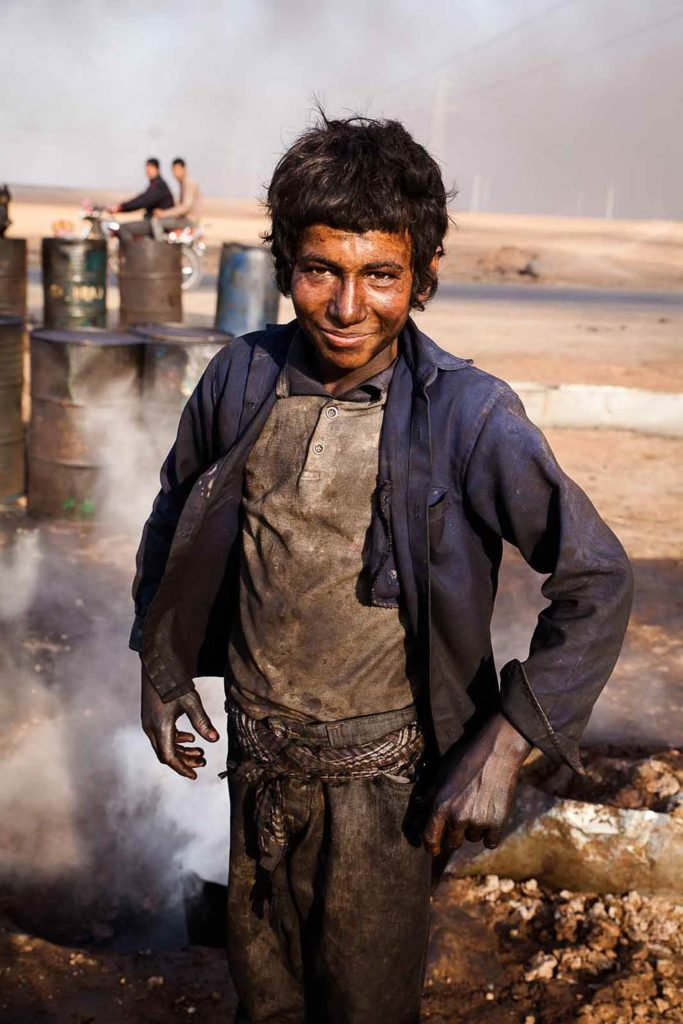 The Chilld Oil: Young boy working at makeshift oil refinery in Hasakah, Syria, 2014 ©Yann Renoult/Wostok Press