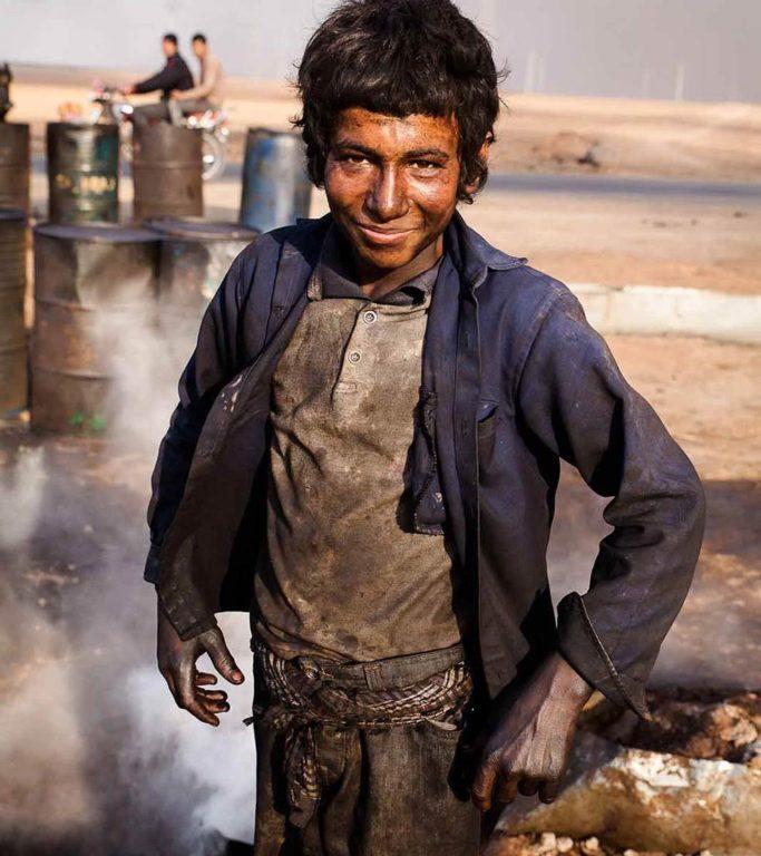 صبي يعمل في مصفاة نفط مرتجلة في الحسكة، سوريا، 2014 (يان رينو/ Wostok Press / من باكس)